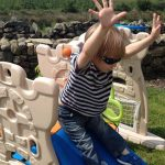 Toddler going down the slide in sunglasses