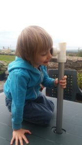 Gabriel looking through a parasol pole pretentding to be a pirate.