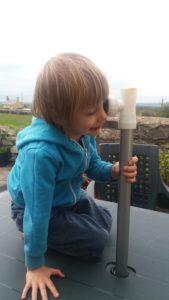 Gabriel looking through a parasol pole pretentding to be a pirate.
